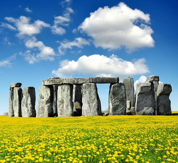 Stonehenge with yellow flowers in foreground against a blue sky with white clouds