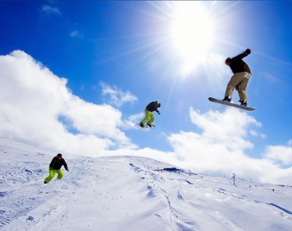 Snowboarders performing tricks in mid air