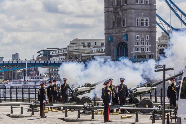 Soldiers fire a Royal Salute in front of Tower Bridge, London