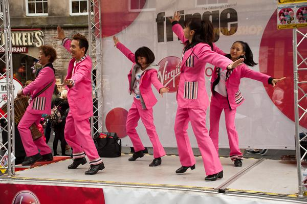 Energetic tap dancers dressed in pink suits on the Royal Mile