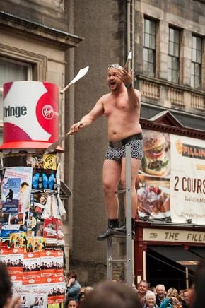 Knife juggler at top of ladder in Edinburgh Festival
