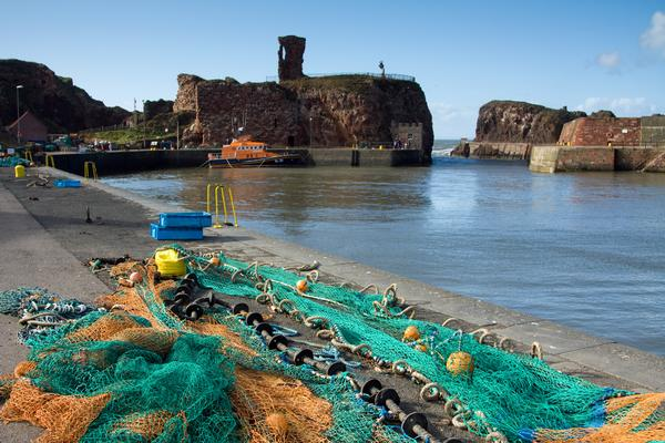 Dunbar Castle seen from harbour with fishing nets in foreground