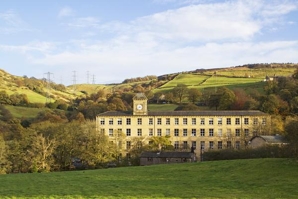 External view of Rishworth Mill in West Yorkshire, with hills in background