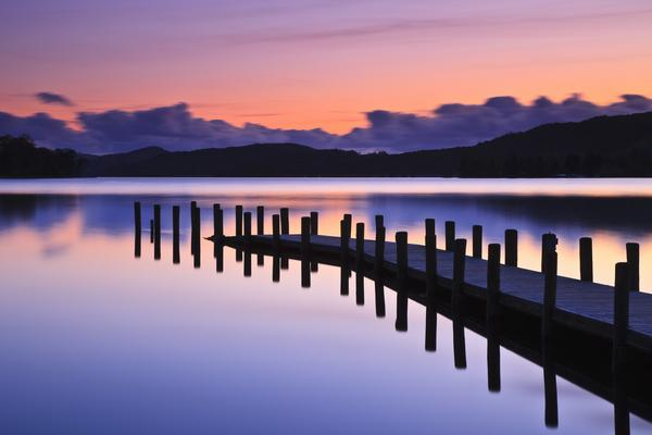 A jetty reflected in the still water of Coniston Water at sunset