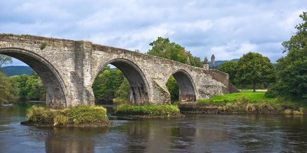 The old bridge across the Forth at Stirling, Scotland, - the pointed tower of the Wallace Monument can be seen in the background