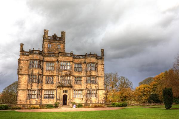 Dramatic image of Gawthorpe Hall with storm clouds in background