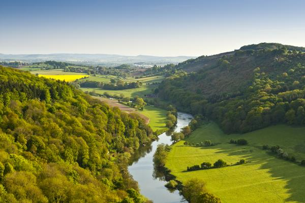 Meandering River Wye making its way through lush green rural farmland in the warm early sunlight