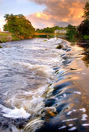 Water running over weir at evening at Grassington, Yorkshire Dales National Park