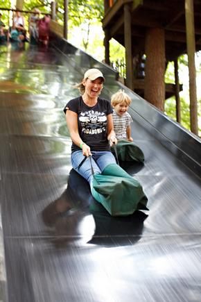 Woman and child going quickly down large slide