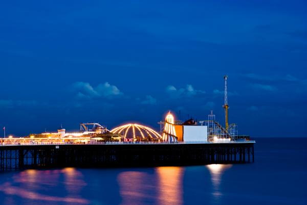 Brighton Pier at night with the funfair illuminated by bright lights