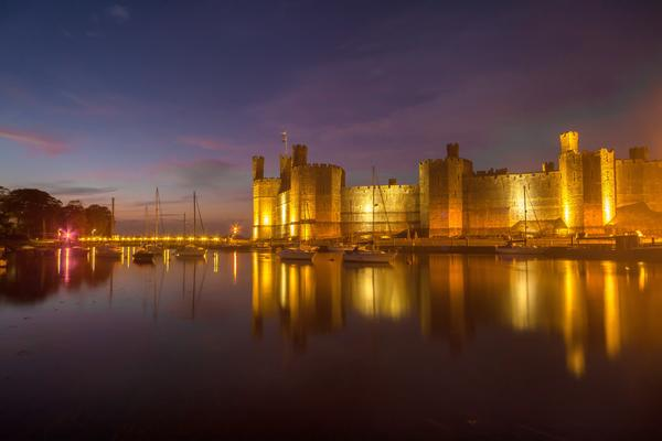 Caernarfon Castle at dusk with yachts floating in the foreground