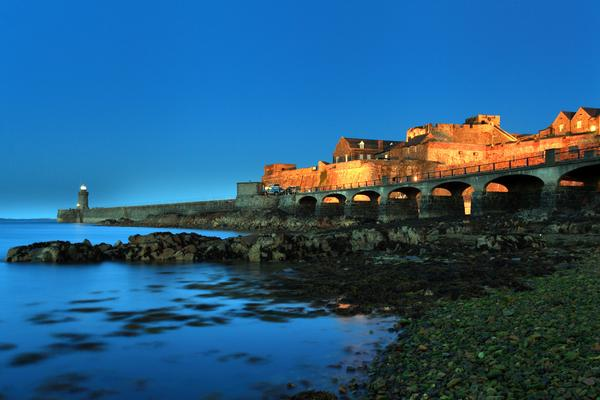 Illuminated Castle Cornet at dusk against a dark blue sky