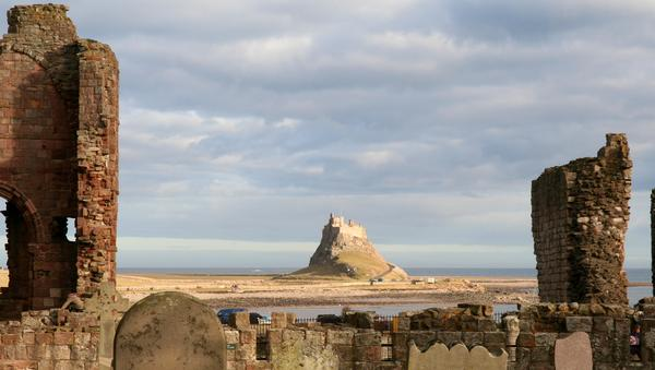 Lindisfarne Castle seen from the graveyard of Lindisfarne Priory.