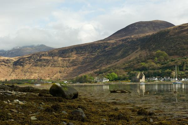 Lochranza Castle seen from a distance with mountains in the background