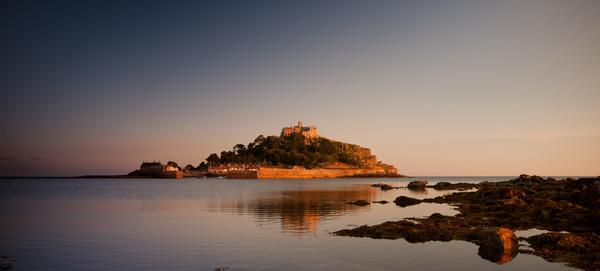 St Michael's Mount, Marazion, Cornwall bathed in light of orange sunset