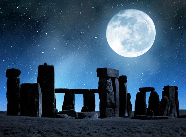 Stonehenge at night with moon and stars overhead