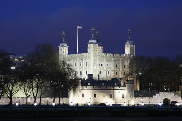 The Tower of London illuminated at night, viewed from the Thames