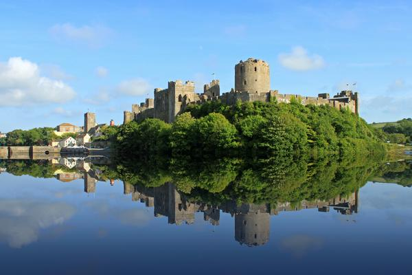 View of Pembroke Castle clearly reflected in still water