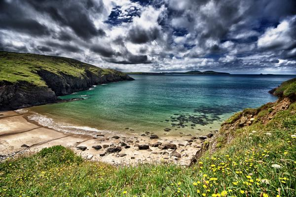 Dramatic sky over a sandy bay at Porth Melgan seen from Pembrokeshire Coast Path