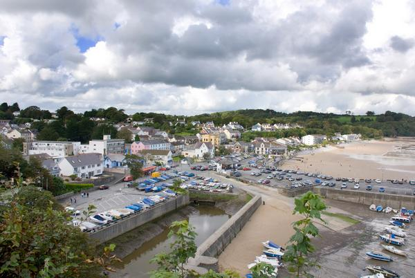 View of Saundersfoot, a Pembrokeshire fishing village and seaside resort showing the beach, and boats in the foreground