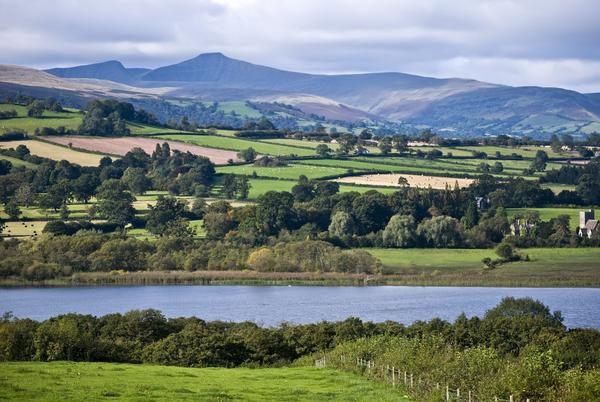 Landscape showing Llangorse Lake, fields, and mountains in the distance, in the Brecon Beacons National Park