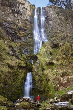 Solitary figure wearing a red coat is dwarfed by the 73 metre Pistyll Rhaeadr Waterfall in Powys