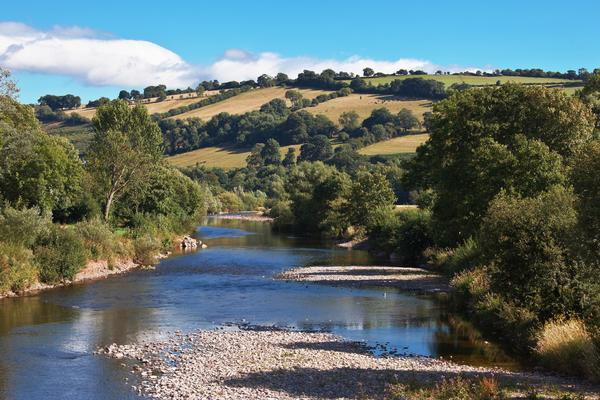 The River Usk flowing through landscape with trees and fields on a sunny day