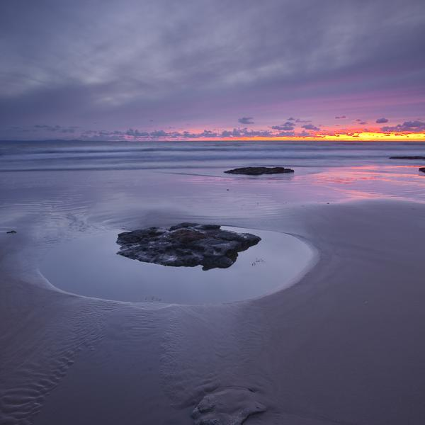Sunset over the wet sand at Dunraven Bay
