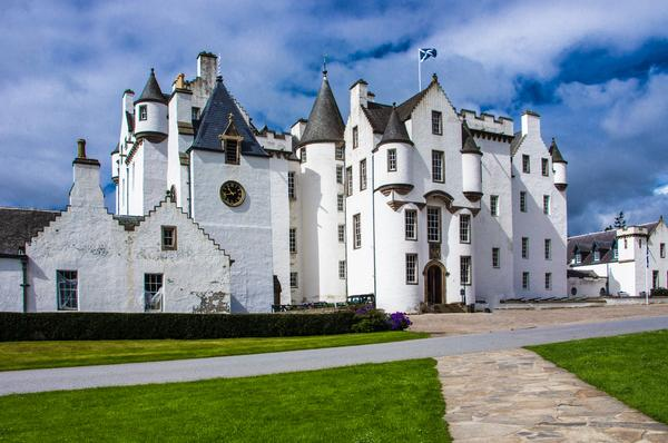 Blair Castle, a white castle with turrets seen against a blue sky with a Saltire flag flying