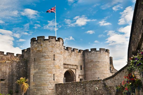 Union flag flies against a blue sky over the main entrance and guard towers to Stirling Castle