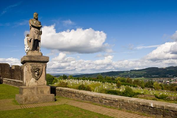 Statue of King Robert The Bruce statue against a blue sky and view to distant hills, in Stirling Castle