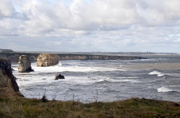 View over Marsden Beach with waves on the sea on a cloudy day