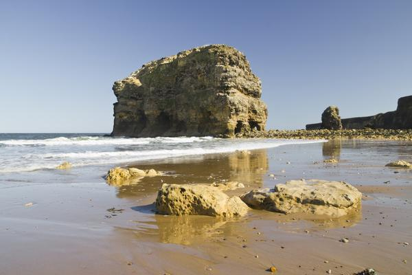 Marsden Rock, South Shields, seen from the beach on a sunny day