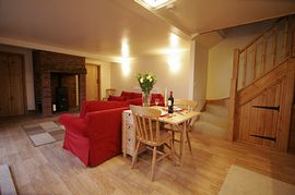Stable Cottage - lounge with wood burner and confortable slog