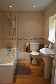 Stylish bathroom with bath, shower, washbasin and toilet.