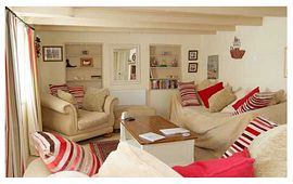 Rosemary Cottage - The living room with squashy sofas and a wood burning stove.