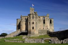 Warkworth Castle against dramatic blue sky © Shutterstock / Gail Johnson