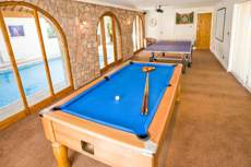 Games Room with pool table in foreground and table tennis table and dartboard in background. An indoor swimming pool is visible through windows on the left.