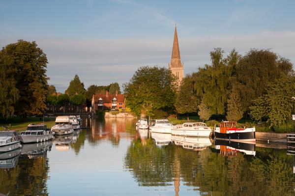 Boats moored on Thames in front of trees and Abingdon Church