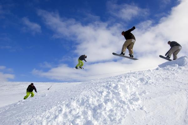 Snowboarders jumping on a sunny day in the Cairngorm Mountains