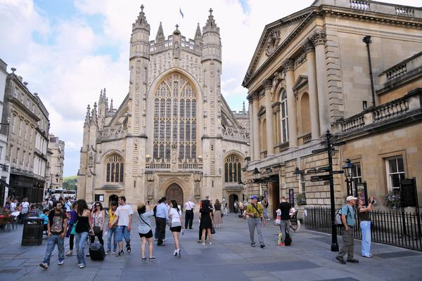 Busy street scene in courtyard of Bath Abbey and the Roman Baths