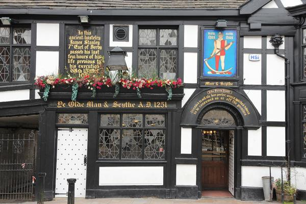 Ye Olde Man and Scythe pub in Bolton, with old fashioned writing on the front.