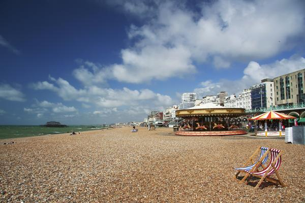 Brighton Beach - pebbles, fun fair rides and striped deck chairs