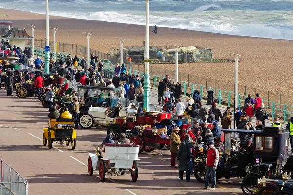 Motor car owners relax on the seafront after completing the annual London to Brighton Veteran Car Rally