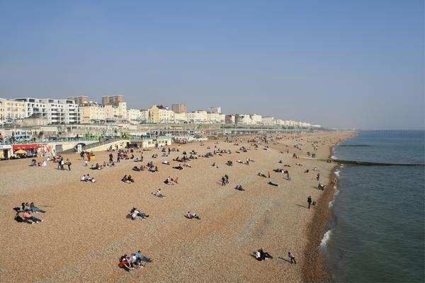 View of people on Brighton Beach, with the line of white hotels and apartments behind