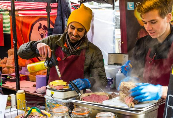 A man melting cheese on burgers using a blow torch at a stall in Camden Food Market