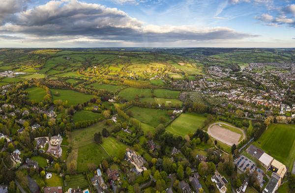 Dramatic aerial view of patchwork farmland and houses with pretty wooded boundaries, in the warm early evening sunshine around Cheltenham