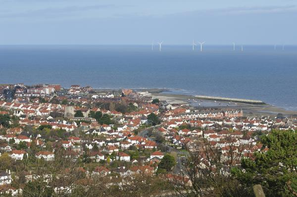 Aerial view of Colwyn Bay with wind turbines in sea in distance