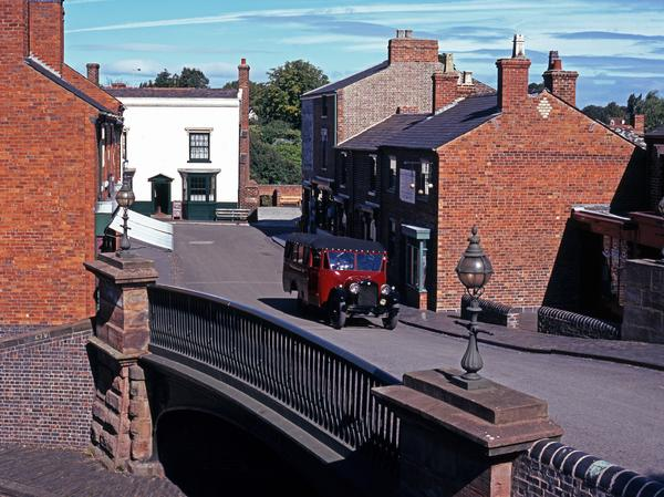 The main village street which has been recreated at the Black Country Living Museum with period car crossing the bridge