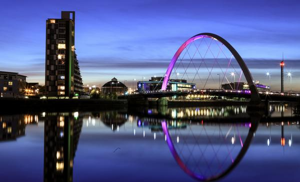 Night view of the Clyde Arc with coloured lighting and reflections in the River Clyde